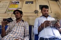 FILE PHOTO: Commuters watch videos on their mobile phones as they travel in a suburban train in Mumbai