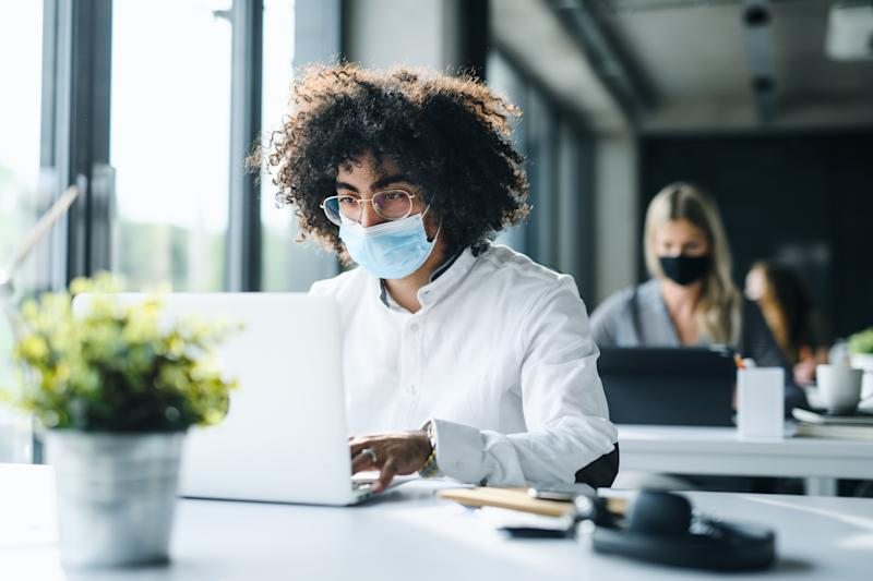 Portrait of young man with face mask back at work in office after lockdown, working.