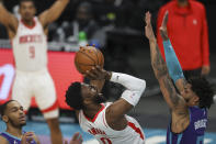 Houston Rockets guard David Nwaba, center, shoots over Charlotte Hornets forward Miles Bridges in the first half of an NBA basketball game in Charlotte, N.C., Monday, Feb. 8, 2021. (AP Photo/Nell Redmond)