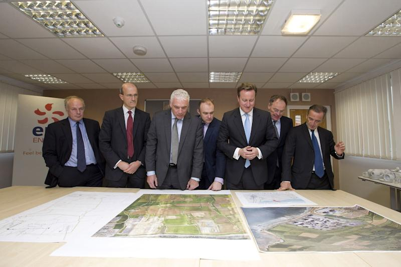 From left: Ian Liddell-Grainger, British Member of Parliament, Humphrey Cadoux-Hudson Managing Director of Nuclear New Build at British Energy Group, Nigel Cann site director of Hinkley Point C, Britain's Energy Secretary, Ed Davey, Britian's Prime Minister David Cameron, Vincent de Rivaz, Chief Executive of EDF (Electricite de France) and Henri Proglio, CEO and Chairman of EDF examine site plans for the new Hinkley C nuclear power station at Hinkley Point, south western England, Monday, Oct. 21, 2013. Britain's first new nuclear power station in a generation is to be built under the 16 billion pound ($26 billion/19 billion euro) project which will create thousands of new jobs. The move followed an agreement between the Government and French-owned EDF Energy, which will see Hinkley Point C begin operating in 2023. (AP Photo/PA, Justin Tallis) UNITED KINGDOM OUT NO SALES NO ARCHIVE