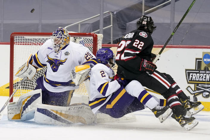 The puck flies past Minnesota State goaltender Dryden McKay (29) as Akito Hirose (2) clears St. Cloud State's Joe Molenaar (22) from the crease during the second period of an NCAA men's Frozen Four hockey semifinal in Pittsburgh, Thursday, April 8, 2021. (AP Photo/Keith Srakocic)