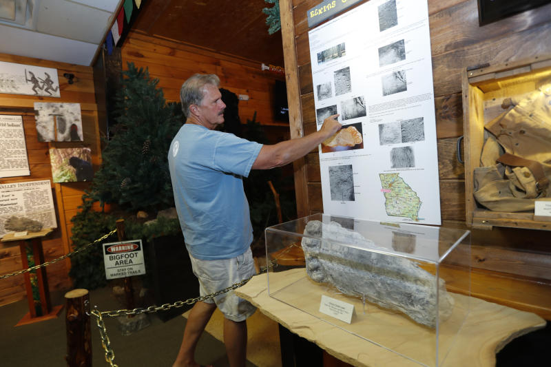 This Aug. 8, 2019, photo shows Bigfoot researcher and museum owner David Bakara pointing to a display at Expedition: Bigfoot! The Sasquatch Museum in Cherry Log, Ga.  Bakara, a longtime member of the Bigfoot Field Researchers Organization who served in the Navy, drove long-haul trucks and tended bar before opening the museum in early 2016 with his wife, Malinda. (AP Photo/John Bazemore)