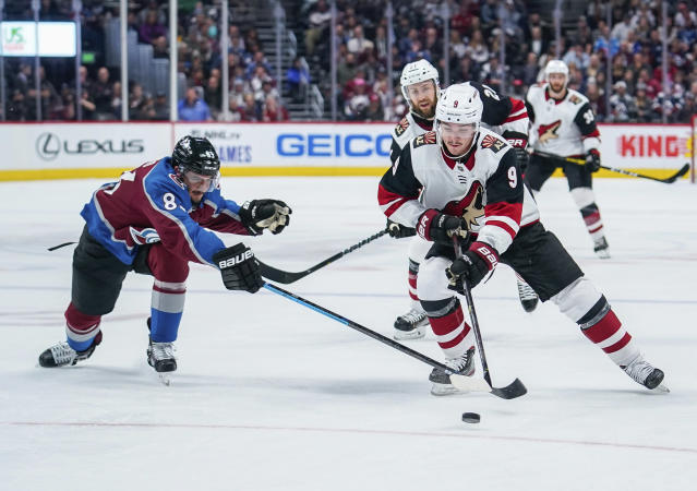 Colorado Avalanche left wing Matt Nieto (83) and Arizona Coyotes center Clayton Keller (9) reach for the puck during the second period of an NHL hockey game, Saturday, Oct. 12, 2019, in Denver. (AP Photo/Jack Dempsey)