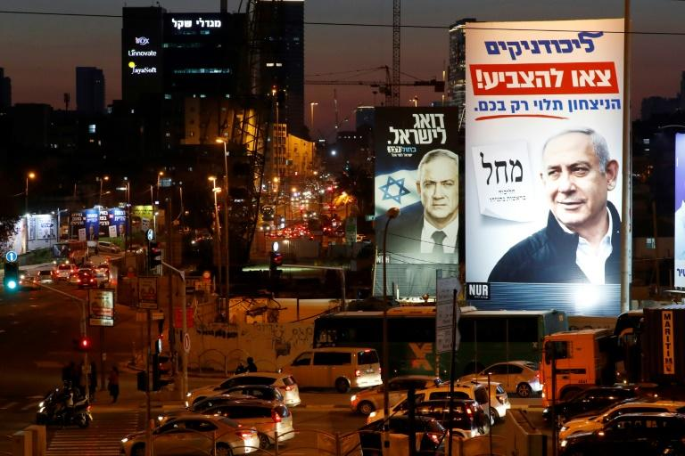 A Blue and White alliance billboard showing Benny Gantz behind a Likud billboard showing Israeli Prime Minister Benjamin Netanyahu, in the city of Bnei Brak (AFP Photo/JACK GUEZ)