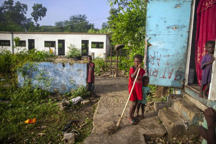 Jonelson Princeton, 7, left, who survived cholera as a newborn, stands near his sister Ritchina Princeton, center, and other siblings where they live with their parents and grandmother in what was once an office on the former U.N. base in Mirebalais, Haiti, Monday, Oct. 19, 2020. Ten years after a cholera epidemic swept through Haiti and killed thousands, families of victims still struggle financially and await compensation from the United Nations as many continue to drink from and bathe in a river that became ground zero for the waterborne disease. (AP Photo/Dieu Nalio Chery)