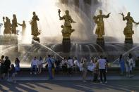 """People cool themselves at a fountain """"Friendship of Peoples"""" at VDNKh (The Exhibition of Achievements of National Economy) in Moscow, Russia, Sunday, June 20, 2021. The hot weather in Moscow is continuing, with temperatures forecast to reach over 30 degrees Celsius (86 Fahrenheit). (AP Photo/Alexander Zemlianichenko)"""