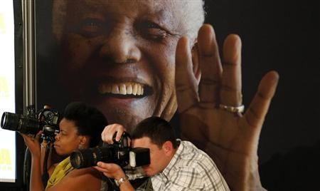 """Photographers take pictures in front of a poster of anti-apartheid leader and former president Nelson Mandela during a news conference with the cast of the biographical film """"Mandela: Long Walk to Freedom"""" at the Nelson Mandela Centre of Memory in Johannesburg, November 2, 2013. REUTERS/Siphiwe Sibeko"""