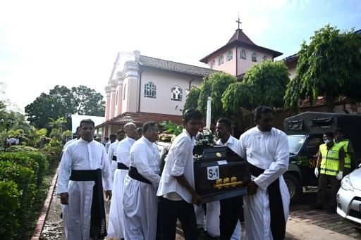 Priests and relatives carry the coffin of a bomb blast victim after a funeral service at St Sebastian's Church in Negombo