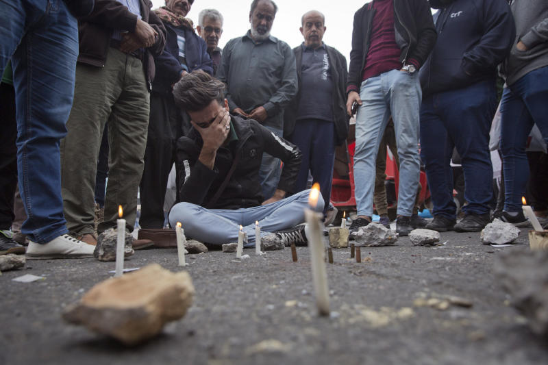 Iraqis gather around a crying man who lit candles by the spot where an Iraqi protester was killed Friday, at Khilani square, in Baghdad, Iraq, Saturday, Dec. 7, 2019. Gunmen in cars opened fire Friday in Baghdad's Khilani square, killing and wounding scores of people.  (AP Photo/Nasser Nasser)