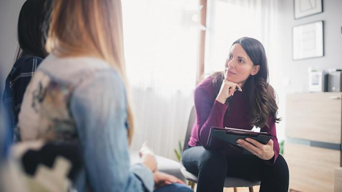 Pregnant counselor advising young lesbian couple at their home.