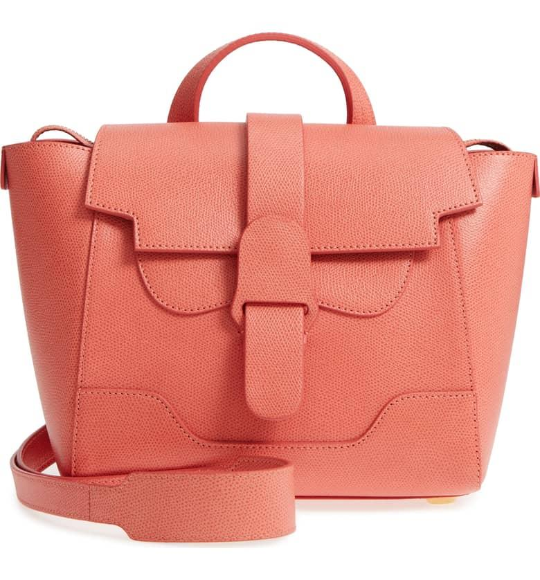 "<p>The Senreve bag is a fan-favorite among working women. Wear it as a backpack, as a crossbody, or just as a tote bag. And now it comes in a bright shade of coral, making it the statement bag you need for 2019. <br /><a rel=""nofollow"" href=""https://fave.co/2PMQQEQ""><strong>Shop it:</strong></a> Mini Maestra Leather Satchel, $695, <a rel=""nofollow"" href=""https://fave.co/2PMQQEQ"">nordstrom.com</a> </p>"
