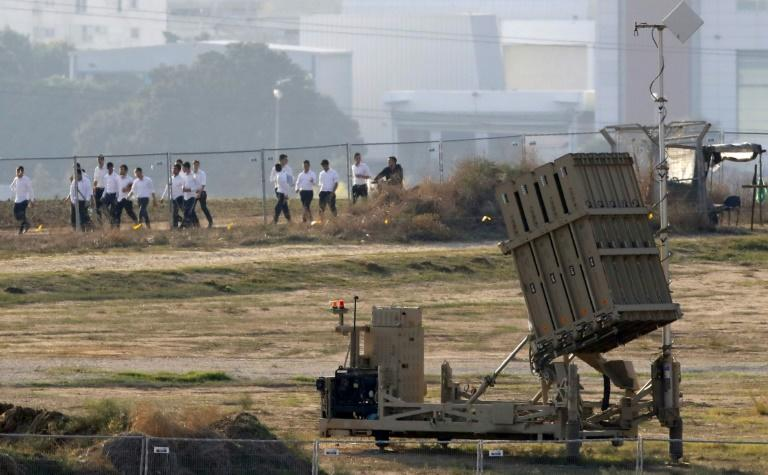 Israeli religious students walk past a battery of Iron Dome defence missile system in the southern Israeli city of Ashdod, neighbouring the Palestinian Gaza Strip