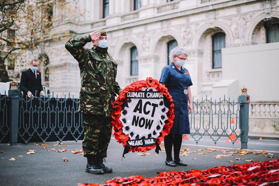 Extinction Rebellion campaigner Donald Bell observed a two-minute silence before hanging a wreath of poppies on the Cenotaph (TheLightscaper/PA)