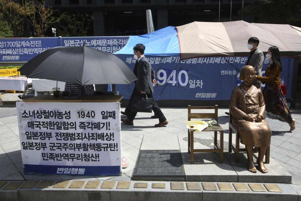 """A protester under an umbrella sits next to a statue symbolizing a wartime sex slave to demand full compensation and an apology for them near Japanese Embassy in Seoul, South Korea, Wednesday, April 21, 2021. A South Korean court on Wednesday rejected a claim by South Korean sexual slavery victims and their relatives who sought compensation from the Japanese government over their wartime sufferings. The banner reads: """"Apology and compensation."""" (AP Photo/Ahn Young-joon)"""