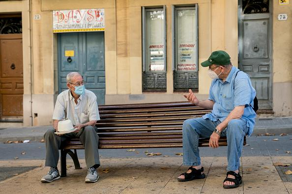 Two men talk on a bench keeping a safe distance and wearing a safety mask in Hospitalet de Llobregat, Spain.