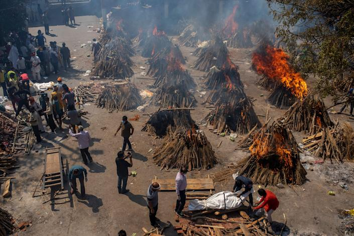 Multiple funeral pyres of victims of COVID-19 burn in an area that has been converted for mass cremation in New Delhi, India, Saturday, April 24, 2021.