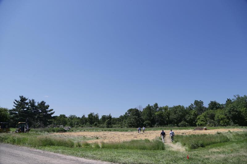 Investigators stand at the scene in Oakland Township, Mich., Wednesday, June 19, 2013 where officials attempt to restore the field to its natural condition after the FBI stopped the search for Jimmy Hoffa's remains. The FBI had been digging and searching for three days for the remains of Teamsters union president Hoffa who disappeared from a Detroit-area restaurant in 1975. (AP Photo/Carlos Osorio)