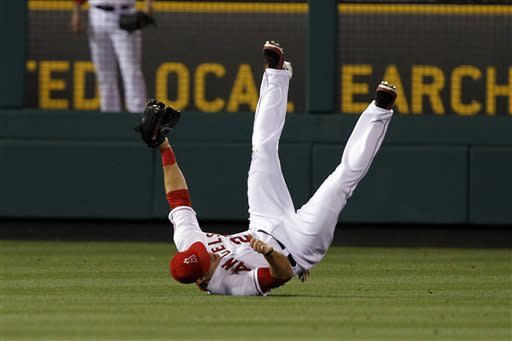 Los Angeles Angels left fielder Mike Trout rolls over after catching a fly ball hit to end sixth inning during a baseball game Friday, April 19, 2013, in Anaheim. (AP Photo/Alex Gallardo)