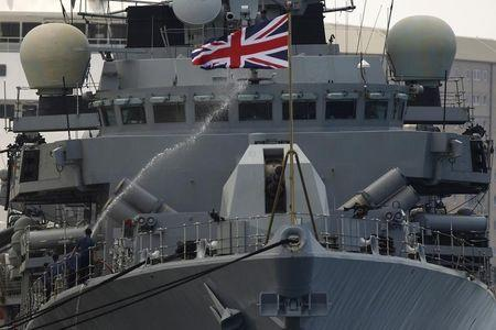 Members of the British Royal Navy frigate HMS Westminster spray water with a hose to clean the ship after arriving at a port in Gibraltar