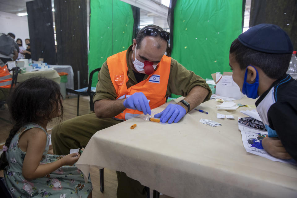 An Israeli soldier conducts a COVID-19 antibody test on a child in Hadera, Israel, Monday, Aug. 23, 2021. Ahead of the opening of the school year on Sept. 1, the Israeli army's Home Front Command is conducting serology tests on children age 3-12 who have not yet tested positive for coronavirus and are not yet listed as recovered, to see if they have antibodies. (AP Photo/Ariel Schalit)