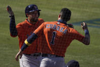 Houston Astros' George Springer, left, is congratulated by Carlos Correa after hitting a solo home run against the Oakland Athletics during the fifth inning of Game 2 of a baseball American League Division Series in Los Angeles, Tuesday, Oct. 6, 2020. (AP Photo/Ashley Landis)