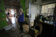 A woman, who did not wish to be identified by name, stands inside of her damaged house after flooding in Pepinster, Belgium, Saturday, July 17, 2021. Residents in several provinces were cleaning up after severe flooding in Germany and Belgium turned streams and streets into raging torrents that swept away cars and caused houses to collapse. (AP Photo/Virginia Mayo)