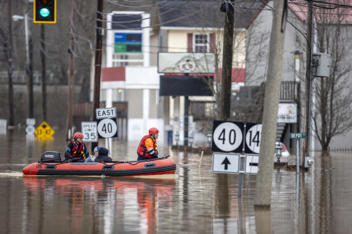 Ricky Keeton, left, of the Oil Springs Fire Department, and Michael Oiler, of the Thelma Fire Department, make their way through floodwaters as they conduct a water rescue following heavy rain in Paintsville, Ky., Monday, March 1, 2021. (Ryan C. Hermens/Lexington Herald-Leader via AP)