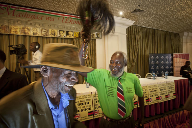 Mau-Mau veteran Mathenge Iregi, 81, waves a a ceremonial whisk to celebrate as he and others await a press conference about an announcement regarding their legal case for compensation against the British Government, in Nairobi, Kenya Thursday, June 6, 2013. The British government is set to announce compensation for Kenyans abused during a rebellion against colonial rule in the 1950s. (AP Photo/Ben Curtis)