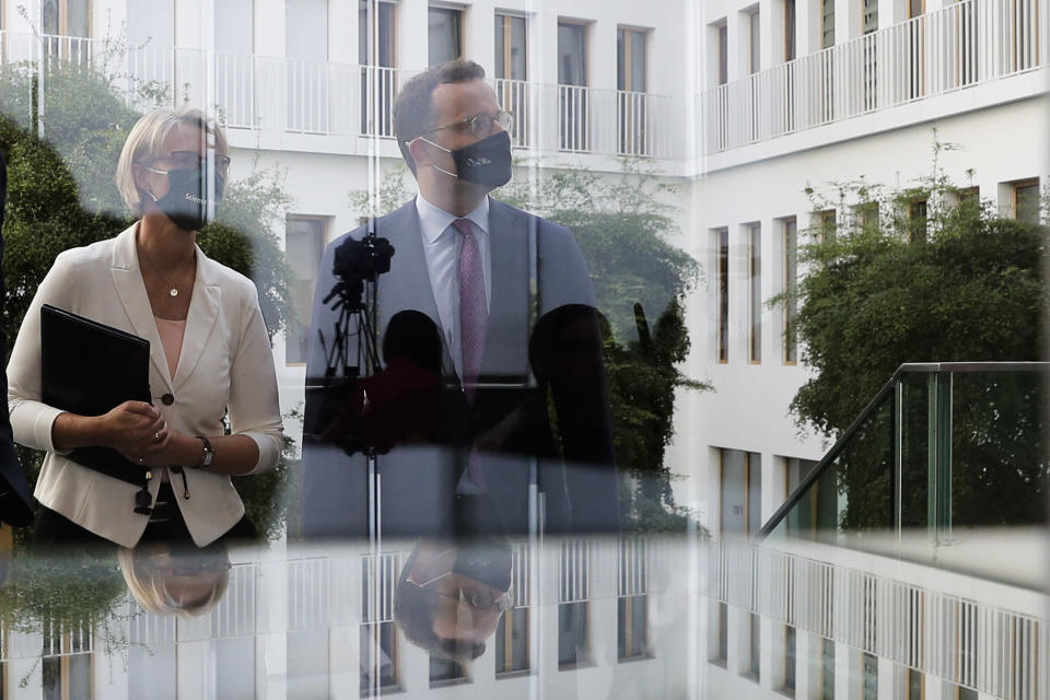 German Health Minister Jens Spahn, right, and Science and Education Minister Anja Karliczek, left, arrive for a news conference about a german program to support the develop a COVID-19 vaccine in Berlin, Germany, Tuesday, Sept. 15, 2020. (AP Photo/Markus Schreiber, Pool)