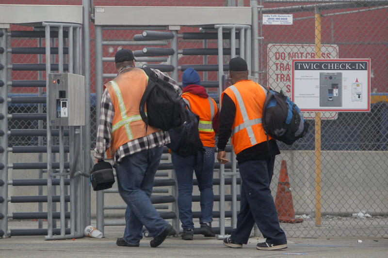 Port workers return to work at the Port of Long Beach Wednesday, Dec. 5, 2012. Work resumed at the Los Angeles and Long Beach harbors after settlement of a strike that crippled the nation's busiest container port complex for more than a week. (AP Photo/Nick Ut)