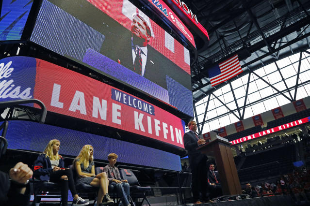 Lane Kiffin, right, speaks to Mississippi fans after being announced as the new NCAA college football coach during a public introduction at The Pavilion, a multipurpose arena on the campus in Oxford, Miss., Monday, Dec. 9, 2019. In attendance were his children, daughters Presley Kiffin, 13, left, Landry Kiffin, 15, second from left, and son Knox Kiffin, 10. Kiffin was previously, the football coach for three years at Florida Atlantic. (AP Photo/Rogelio V. Solis)