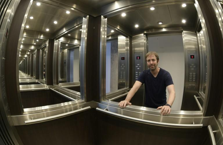 """Erlich poses inside his work """"Elevator Maze, 2011"""" at his studio in Buenos Aires"""