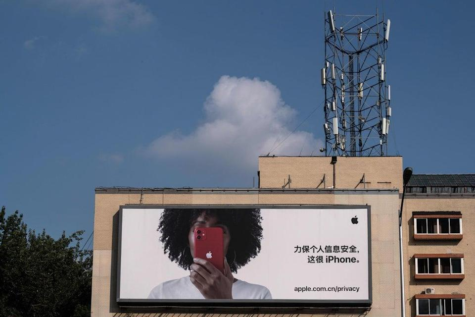 A cellphone tower on top of a building is seen next to a commercial billboard for the iPhone in Beijing (AFP via Getty Images)