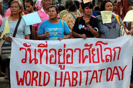 Members of Khon Kaen Slum Network community group hold a banner during a rally outside the United Nations building in Bangkok, Thailand, October 3, 2016. REUTERS/Chaiwat Subprasom