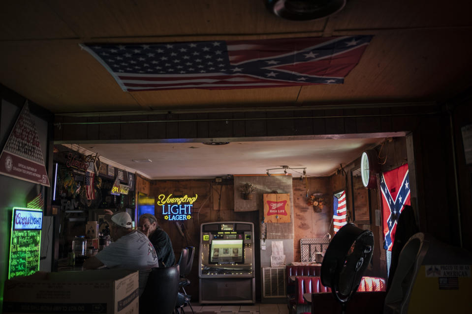 People sit in a bar decorated with an American flag and confederate flags before noon in Meridian, Miss., Wednesday, Oct. 7, 2020. Today, voters in Mississippi face a series of government-created barriers that make it, according to a study in the Election Law Journal in 2018, far and away the most difficult state in which to vote. (AP Photo/Wong Maye-E)