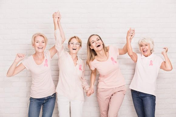 Four women wearing pink breast cancer ribbons standing against a white brick wall and smiling with arms raised.