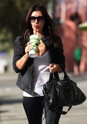 Kim Kardashian wearing her Balenciaga bag  Busted! Kim clearly liked the design and tried to replicate it for her own line. Betcha she'll only wear the real thing, while her fans will use the more affordable imitation. Photo by: courtesy of Splash News