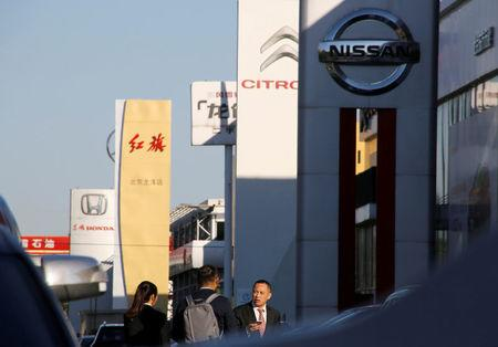 People walk near the showrooms of Chinese and foreign car dealerships in Beijing