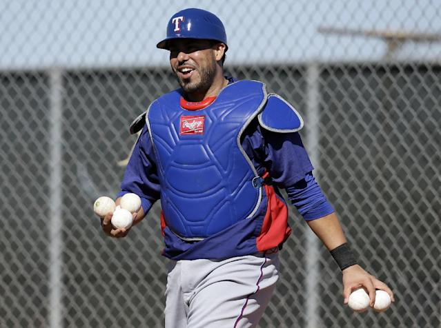 Texas Rangers' Geovany Soto returns balls to a bucket after warming up in the bullpen during spring training baseball practice, Monday, Feb. 17, 2014, in Surprise, Ariz. (AP Photo/Tony Gutierrez)