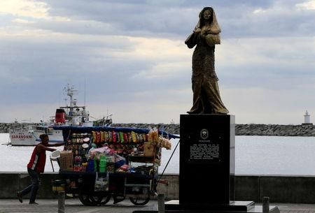 """A vendor pushes a cart past a memorial statue that commemorates the Filipino """"comfort women"""" who worked in Japanese military brothels during World War II, erected along a main street of Roxas Boulevard, Metro Manila, Philippines January 12, 2018. A message reads """"This monument is in honor of Filipino women who were victims of abuse during the Japanese occupation of the Philippines (1942-1945). A long time has passed before they testified and revealed what they went through"""". REUTERS/Romeo Ranoco"""