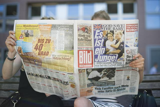 BERLIN, GERMANY - JULY 23: Women read a newspaper the day after the birth of the son of Prince William, Duke of Cambridge and Catherine, Duchess of Cambridge on July 23, 2013 in Berlin, Berlin. The Duchess of Cambridge yesterday gave birth to a boy at 16.24 BST and weighing 8lb 6oz, with Prince William at her side. The baby, as yet unnamed, is third in line to the throne and becomes the Prince of Cambridge. (Photo by Timur Emek/Getty Images)