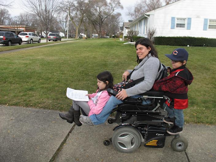 """In this Monday, Nov. 19, 2012 photo, twins Abigail and Noah Thomas, 8, ride on the motorized wheelchair of their mother, Jenn Thomas, on their way to a school book fair in Arlington Heights, Ill. Thomas, a 36-year-old mom who has cerebral palsy, says her twins occasionally complain about having to do a few extra chores around the house to help her. Abigail nods and smiles upon hearing this, but says for the most part, their lives are """"kind of normal."""" For her, having a mom with a disability is just how it is, she says, shrugging. (AP Photo/Martha Irvine)"""