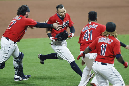 Cleveland Indians' Cesar Hernandez, center, is mobbed by Austin Hedges (17), Carlos Santana (41) and Jose Ramirez (11) after hitting a winning single off Pittsburgh Pirates relief pitcher Chris Stratton during the ninth inning of a baseball game, Friday, Sept. 25, 2020, in Cleveland. (AP Photo/Ron Schwane)