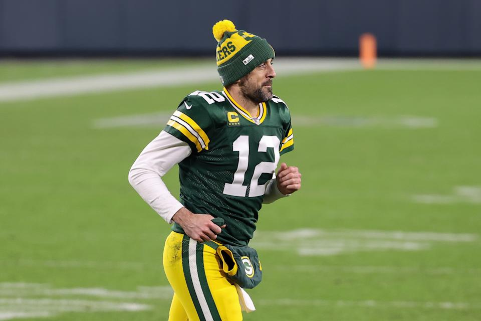 GREEN BAY, WISCONSIN - JANUARY 16: Aaron Rodgers #12 of the Green Bay Packers jogs across the field after beating the Los Angeles Rams 32-18 during the NFC Divisional Playoff game at Lambeau Field on January 16, 2021 in Green Bay, Wisconsin. (Photo by Dylan Buell/Getty Images)