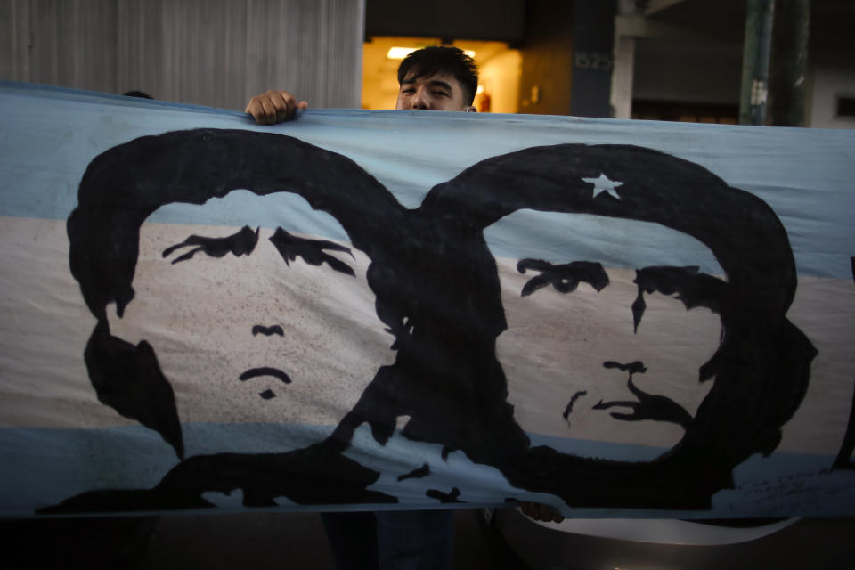 "A soccer fan stands behind a banner featuring former soccer star Diego Maradona and Marxist revolutionary Ernesto ""Che"" Guevara, outside the Clinica Olivos, where Maradona will undergo surgery, in Buenos Aires, Argentina, Tuesday, Nov. 3, 2020. His personal doctor Leopoldo Luque, who is a neurologist, said Maradona has suffered a subdural hematoma, likely caused by an accident. The 1986 World Cup champion was admitted to a private hospital in la Plata with signs of depression on Monday, three days after his 60th birthday. (AP Photo/Natacha Pisarenko)"