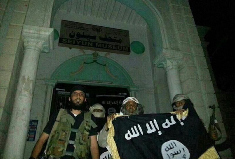 A picture taken with a mobile phone early on May 24, 2014 shows Al-Qaeda militants posing with the Al-Qaeda flag in front of a museum in Seiyun, second Yemeni city of Hadramawt province