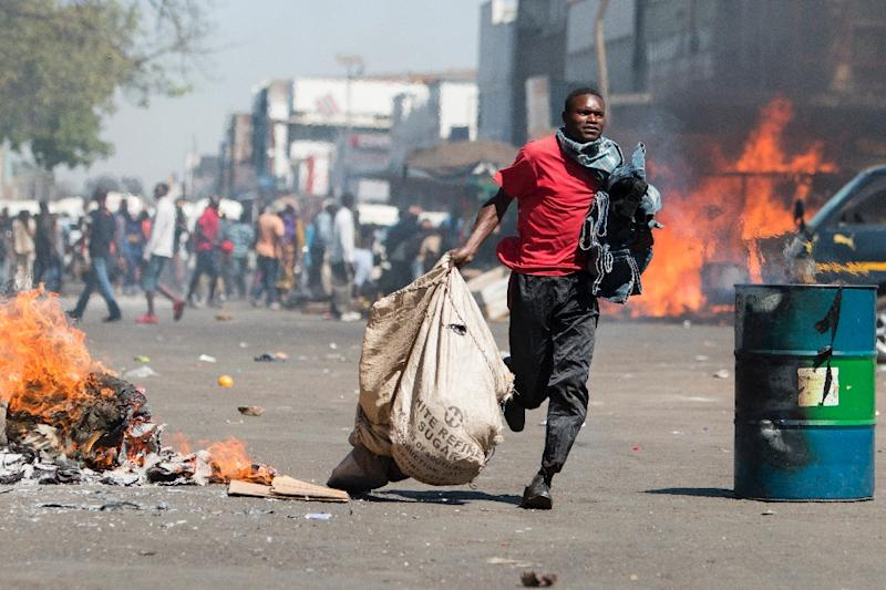 A street vendor flees with his goods as Zimbabwe opposition supporters clash with police in Harare on August 26, 2016 (AFP Photo/Wilfred Kajese)