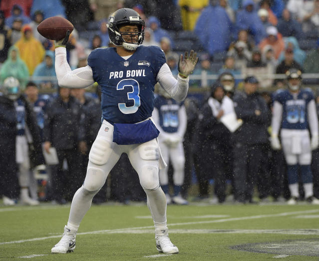 """FILE - In this Jan. 27, 2019, file photo, NFC quarterback Russell Wilson of the Seattle Seahawks throws a pass against the AFC during the first half of their NFL Pro Bowl football game in Orlando, Fla. Wilson posted a video to social media early Tuesday, April 16, 2019, saying, """"Seattle, we got a deal,"""" shortly after a reported midnight deadline for the Seahawks and their star quarterback to agree on a contract extension. Wilson's current $87.6 million, four-year deal was signed at the beginning of training camp in 2015 and was set to expire after next season. (AP Photo/Phelan Ebenhack, File)"""
