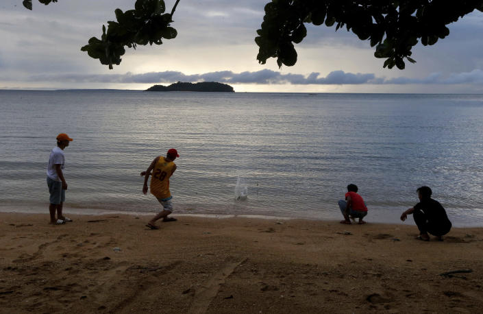 In this Jan. 27, 2019 photo, four boys play by the shore at a beach resort in Talustusan on Biliran Island in the central Philippines. Since December 2018, the small village has been rocked by controversy after about 20 boys and men, including these four, accused their Catholic parish priest Father Pius Hendricks of years of alleged sexual abuse. (AP Photo/Bullit Marquez)