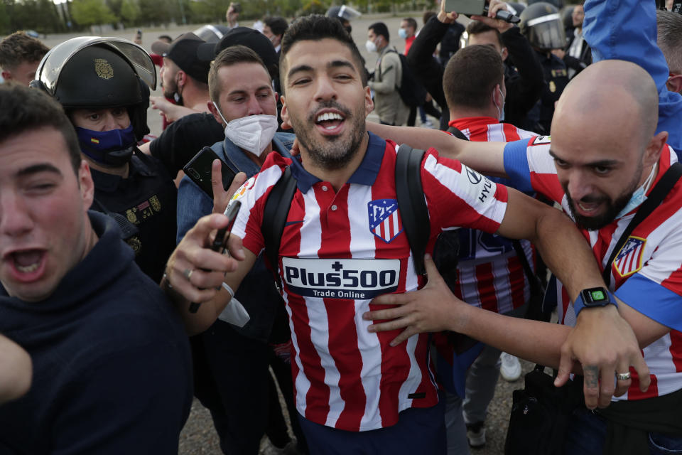 Atletico Madrid's Luis Suarez celebrates with supporters after the Spanish La Liga soccer match between Atletico Madrid and Valladolid at the Jose Zorrilla stadium in Valladolid, Spain, Saturday, May 22, 2021. Atletico won 2-1 and clinches its 11th Spanish La Liga title. (AP Photo/Manu Fernandez)